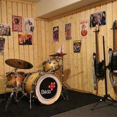 Replokal med gitarrer och affischer på väggarna