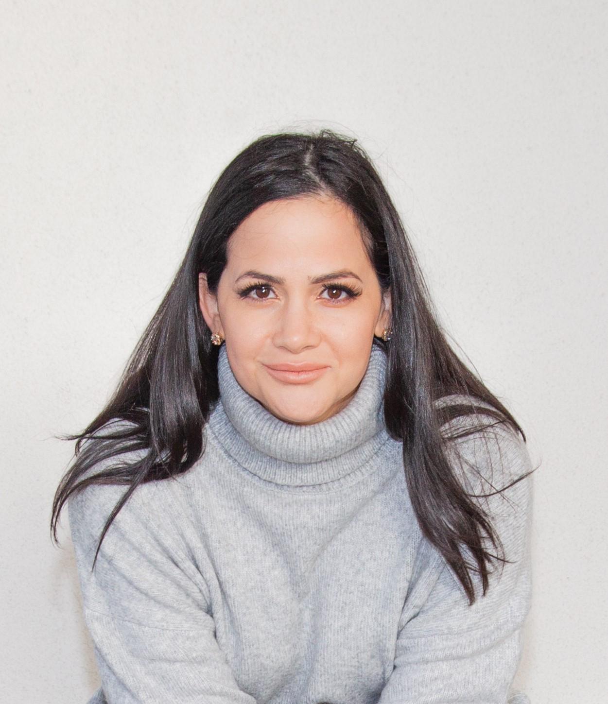 Personalfoto på Suzanne Cronstam. Foto tagit rakt framifrån. Suzanne har mörkt långt hår och har på sig en stickad grå polotröja och bakom henne är en grå vägg.