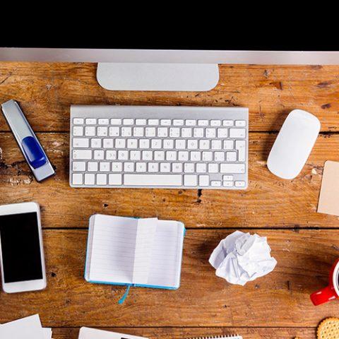 Ett skrivbord med datorskärm, telefon, äpple och andra saker på