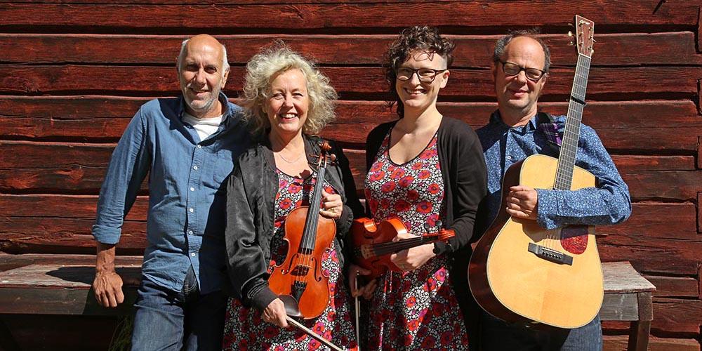 Fyra personer med instrument framför timrad husfasad.