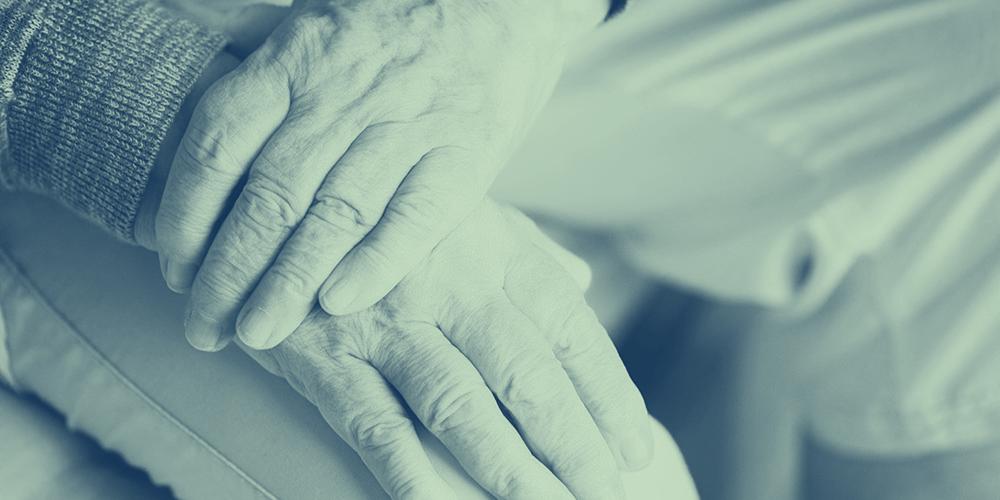 Händer som ligger i ett knä